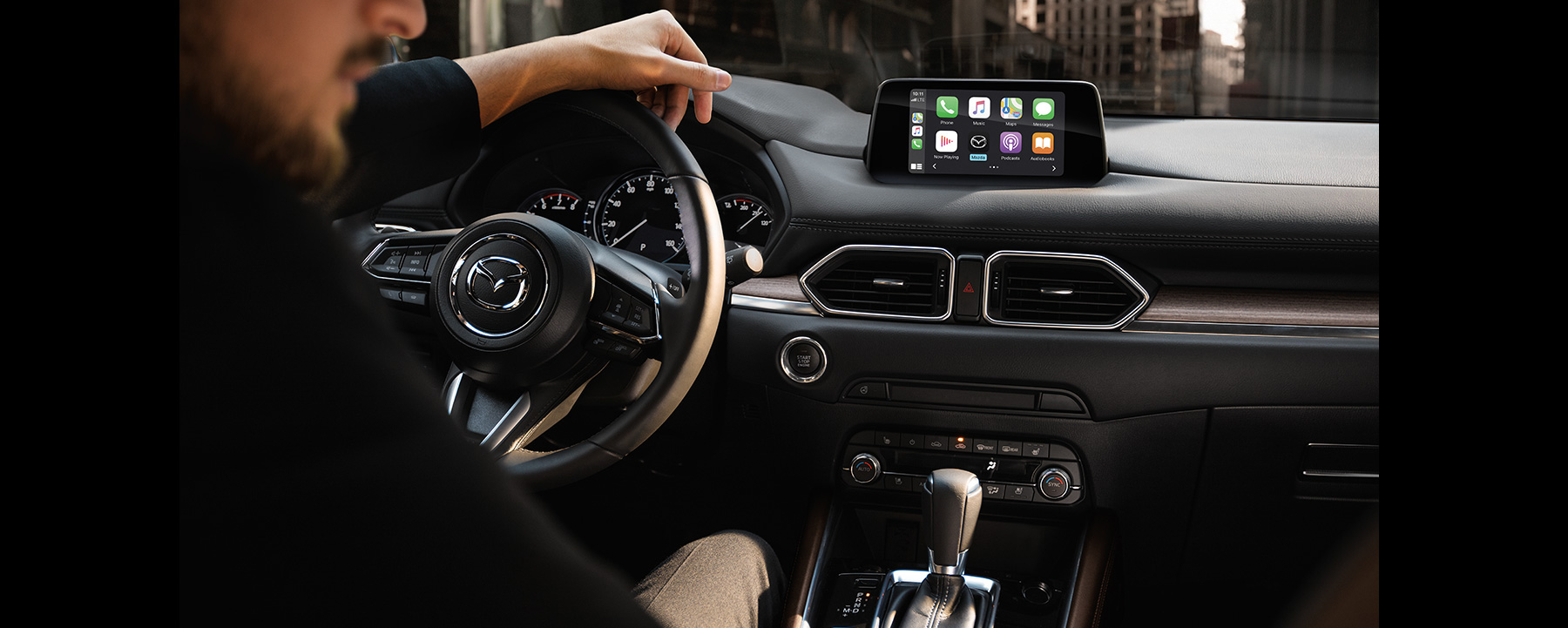 Man driving a Mazda CX-5 with Apple Carplay in view